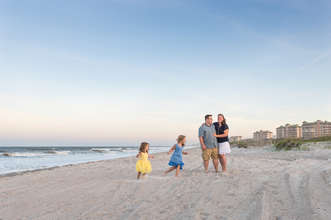 Mom and Dad standing on the beach at sunset with two little girls in yellow and blue dresses running around them