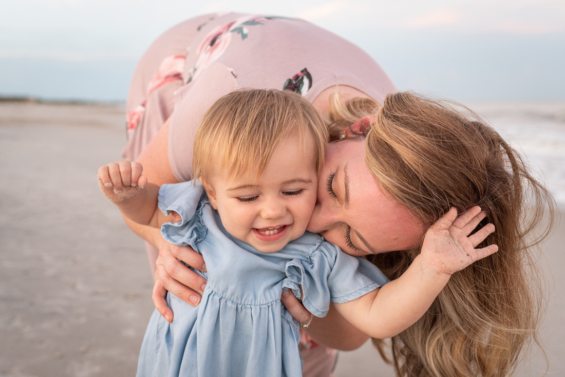 Mom in pink dress kissing one-year old smiling baby girl in blue dress on the beach at sunset
