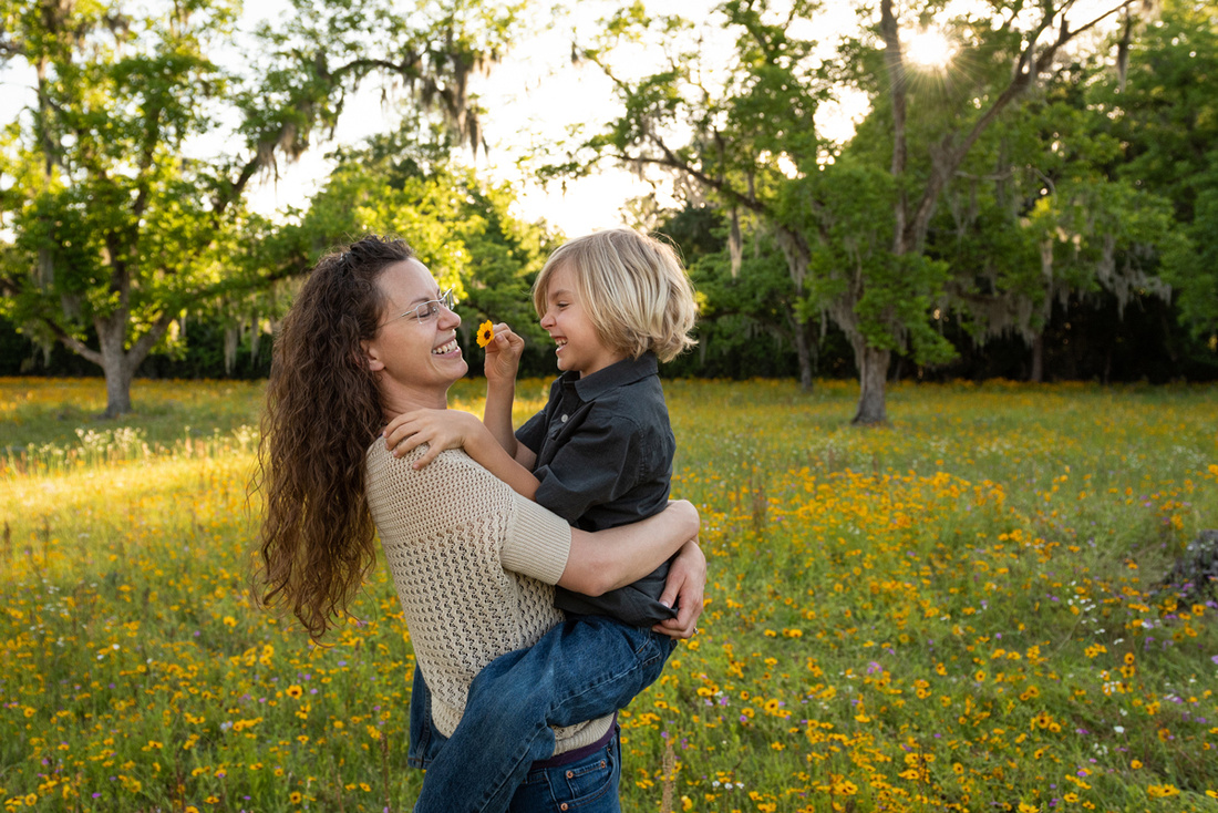 mother holding her son in a flower field and laughing together