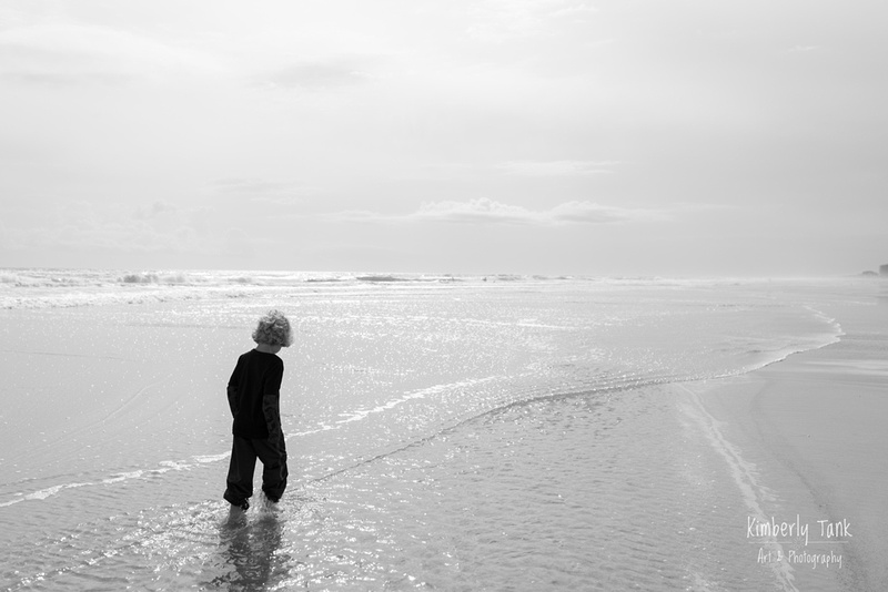 boy walking in the water at the beach