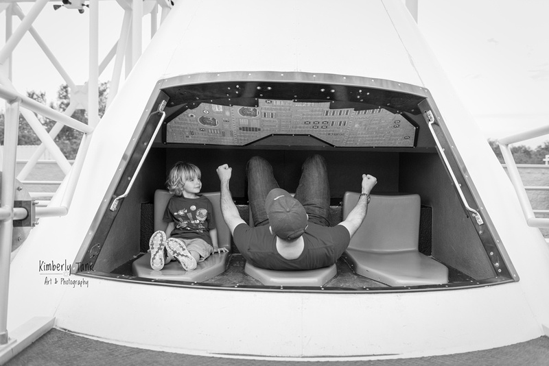 boy and dad in Apollo capsule model at Kennedy Space Center