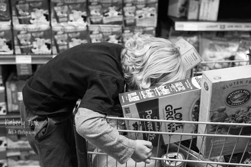 boy in a shopping cart at Whole Foods